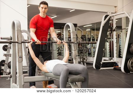 Personal Trainer Spotting A Woman At The Gym