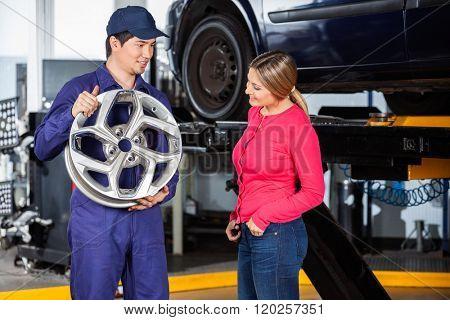 Mechanic Showing Hubcap To Customer