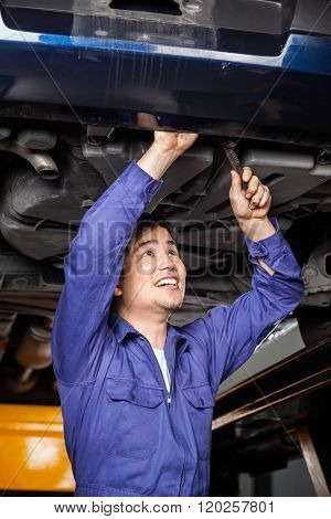 Mechanic Repairing Under Lifted Car