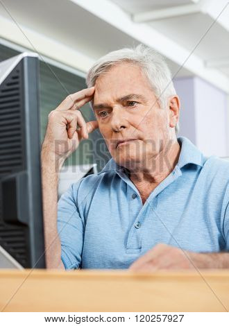 Worried Senior Student Looking At Computer In Class