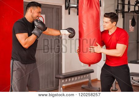 Two Male Friends Training Box At A Gym
