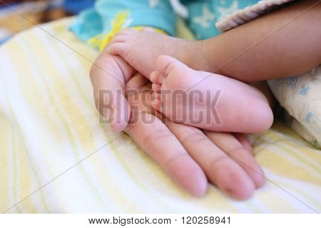 Baby feet in mom hand on age approximately one month.