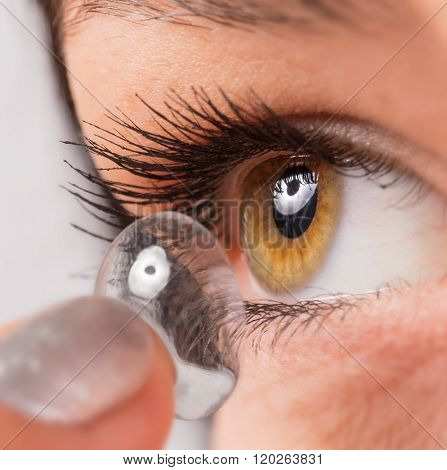 Young woman putting contact lens in her eye. Macro shot.