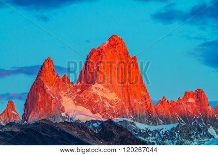 Sharp tops fantastically beautiful cliffs Fitz Roy illuminates the crimson sunset. Amazing Patagonia in February