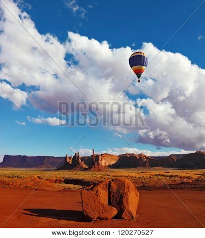 Huge balloon flies over the red desert. Monument Valley in the Navajo Indian Reservation. Arizona, USA