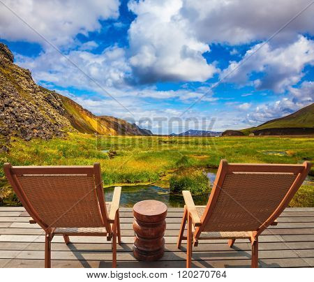 Two comfortable wooden chairs and small table stand for tired tourists.  Volcanic summer tundra. Travel to Iceland in July