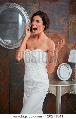 Young bride talking on mobilephone, gesturing and shouting upset.