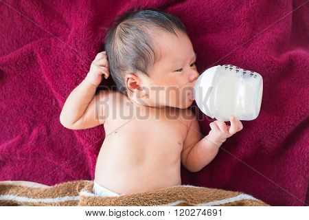 Newborn baby infant eating milk from bottle.
