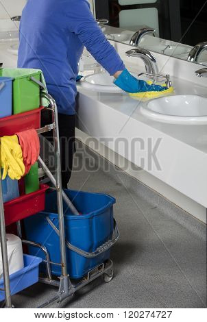 a cleaner is cleaning sink with duster