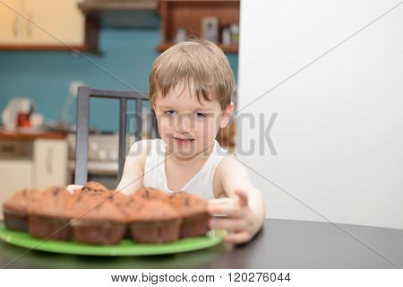 4 Year Old Boy Reaching For A Chocolate Cake