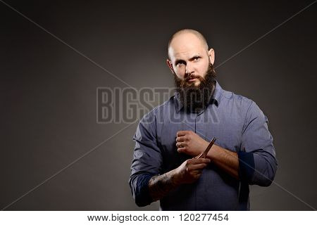 Man With A Beard Holding A Pair Of Scissors