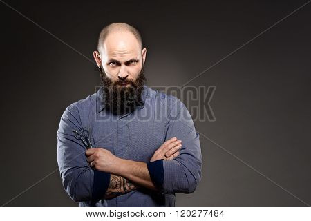 Bald Man With A Beard Holding A Pair Of Scissors. Crossed Hands