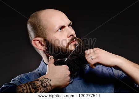 Bald Man With A Beard Shortens His Beard