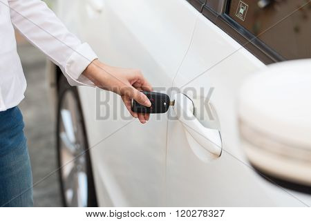 Female hand open the white car on key system automatic.