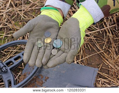 Searching with metal detector - coins in hand