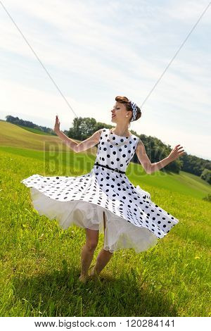 Pin Up Girl Is Dancing And Twisting On The Meadow