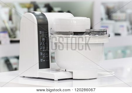 single electric food processor at retail store shelf, defocused background