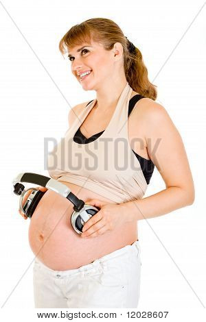 Happy pregnant woman holding headphones on her belly isolated on white