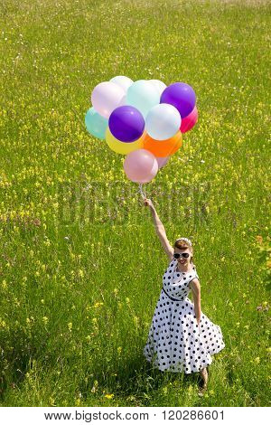 Pinup Girl With A White Petticoat Dress And Balloons On The Meadow