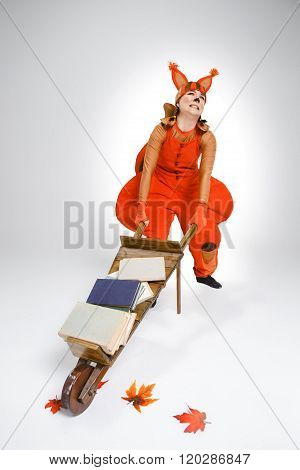Young woman in image of squirrel with cart and books