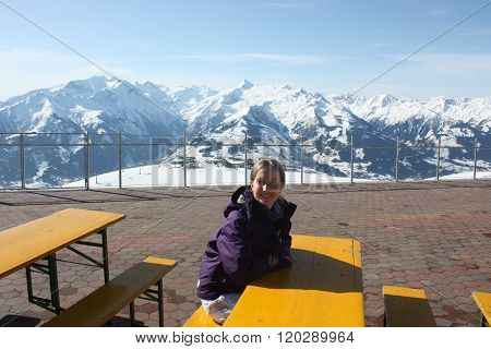 Young Beautiful Snowboarder Woman Sitting On The Table.
