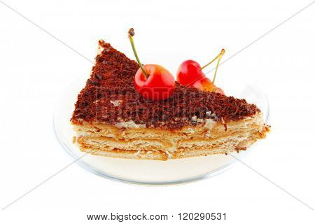 cake and cherry on transparent saucer over white