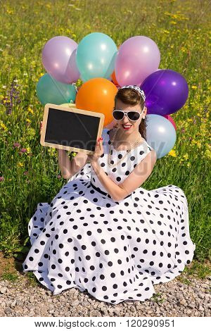 Girl With A 50´s Petticoat Dress Sitting In A Meadow And Holding A Board With Copyspace