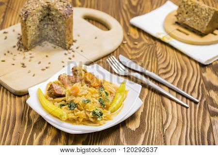 Cooked Cabbage with Carrots, Hot Peppers, Parsley, Integral Sunflower Bread on Brown Wooden Table