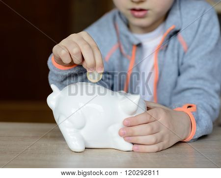 Little Boy Putting The 1 Euro Coin