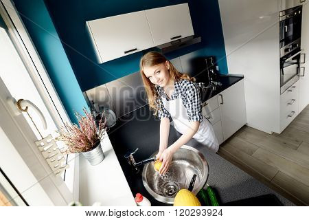 Beautiful Blond Woman Washes The Dishes