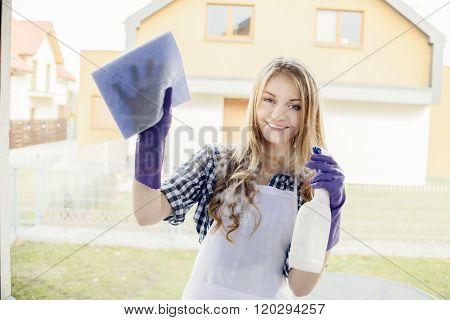 Attractive Young Woman Cleaning Windows In The House