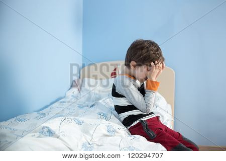 Sad, Upset Little Boy Sitting On The Edge Of His Bed.