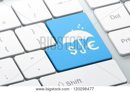 Protection concept: Money And Umbrella on computer keyboard background