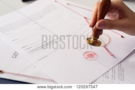 Close Up On Woman's Notary Public Hand Ink Stamping The Document