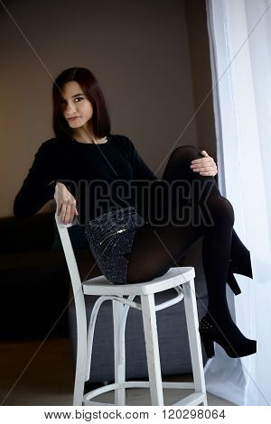 Portrait Of  Woman Sitting On The Barstool.