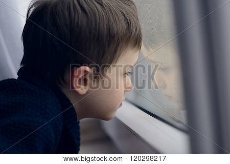Little Boy Waiting By Window For Stop Raining.