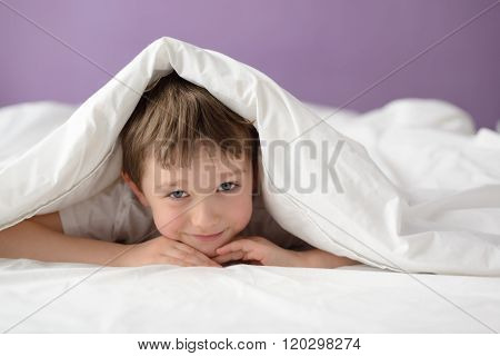 Happy Boy Hiding In Bed Under A White Blanket Or Coverlet