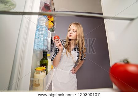 Blonde Woman Pulls Tomato From The Refrigerator.