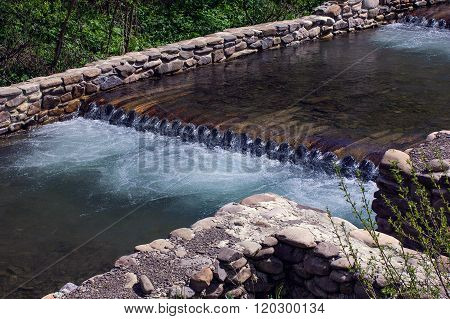 River Flows Through The Wooden Logs Fenced By Stone Foundation
