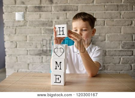 6 Years Boy Holding Playing Wooden Bricks With Letters Making Word Home