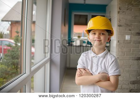 Little 6 Year Old Boy Posing By A Window With A Yellow Helmet