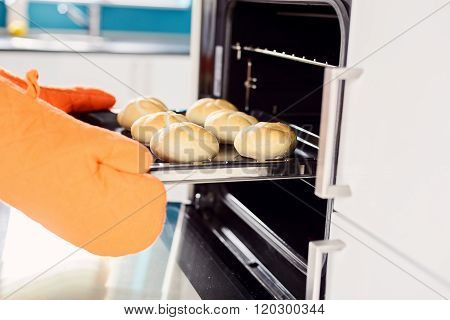 Close Up Of Baker Hands Taking Out Hot Rolls From The Oven.