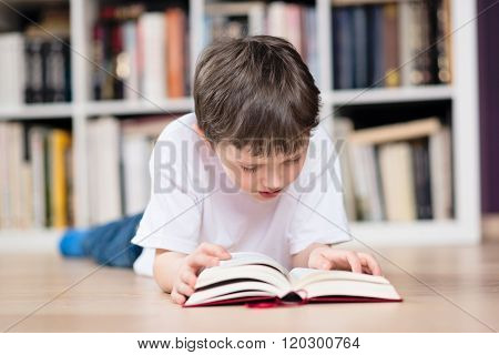 Boy Lies On His Stomach And Reading A Book In The Library