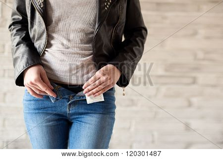 Woman Unbuttons Her Jeans Trousers And Holds A Condom In Her Hand