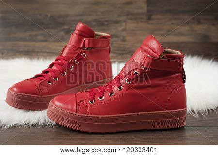 Red Leather Sneakers On A White Carpet And Wood Flooring. Wooden Background