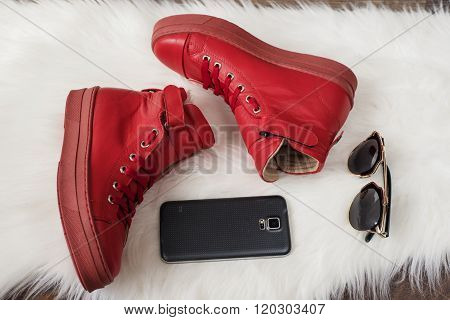 Red Leather Sneakers, Cell Phone, Sunglasses On A White Carpet. Wood Floor.