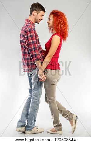 Happy young couple in love looking at each other on grey background