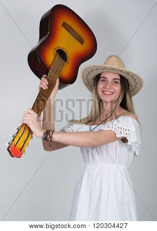 beautiful young leggy blond Country girl in a litl white dress and cowboy hat with a guitar.