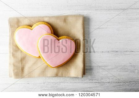Valentine heart cookies with napkin on wooden table, top view