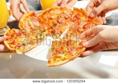 Friends hands holding hot pizza, close up